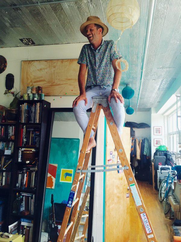Jeremy Gustin dans son loft à New York. Derrière lui, en hauteur, le cadre et sa feuille.